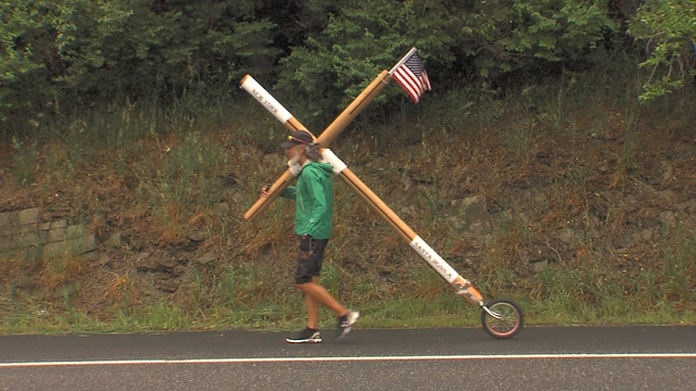 Man carries cross to promote peace, love_126902