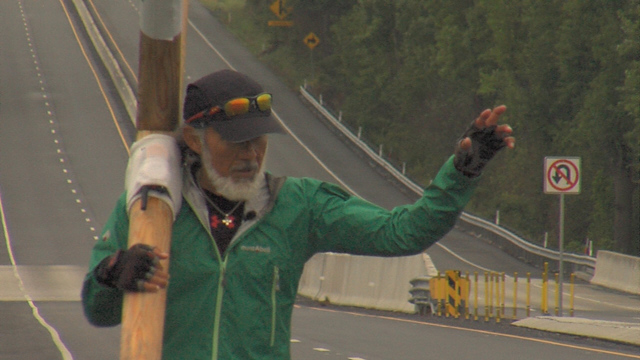 Man carries cross to promote peace, love